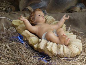 Christkind, etwas kitschig, wie eine Puppe in einer Holzschale liegend, die wiederum im Stroh liegt