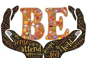 """In zwei Händen, in denen Worte wie """"feel, hold, sense, attend, receive"""" stehen, wird das große Wort """"BE"""" gehalten, das viele Emojis enthält"""