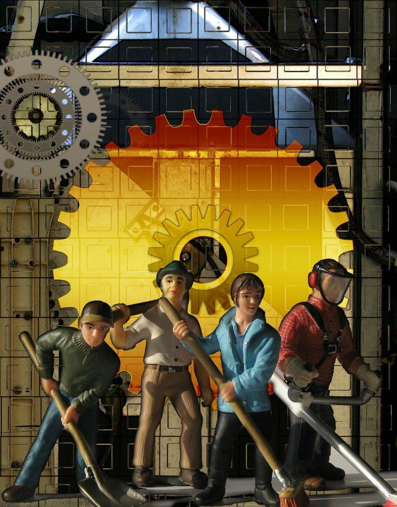 Vier Arbeiter mit Schaufel, Besen, Laubbläser usw. stehen vor Zahnrädern