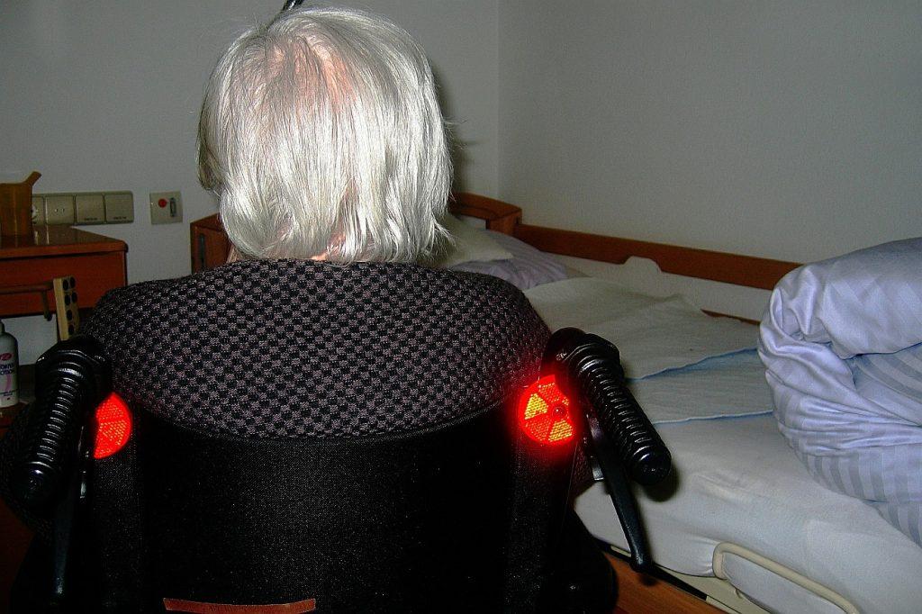 Liebe, die zur Freude führt: Das Bild zeigt von hinten eine Frau im Rollstuhl vor ihrem Bett im Altenheim
