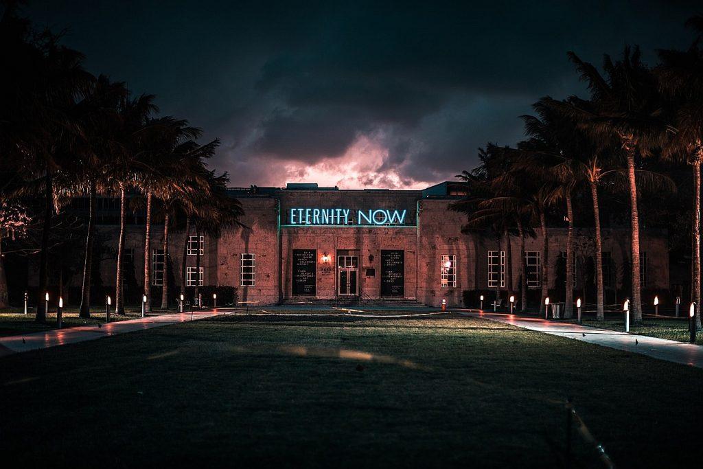 """Ewiges Leben jenseits vom Besitzdenken: Das Bild zeigt ein Gebäude in einer düsteren Abendlandschaft mit dem Schriftzug """"Eternity Now"""" = """"Ewigkeit jetzt"""""""