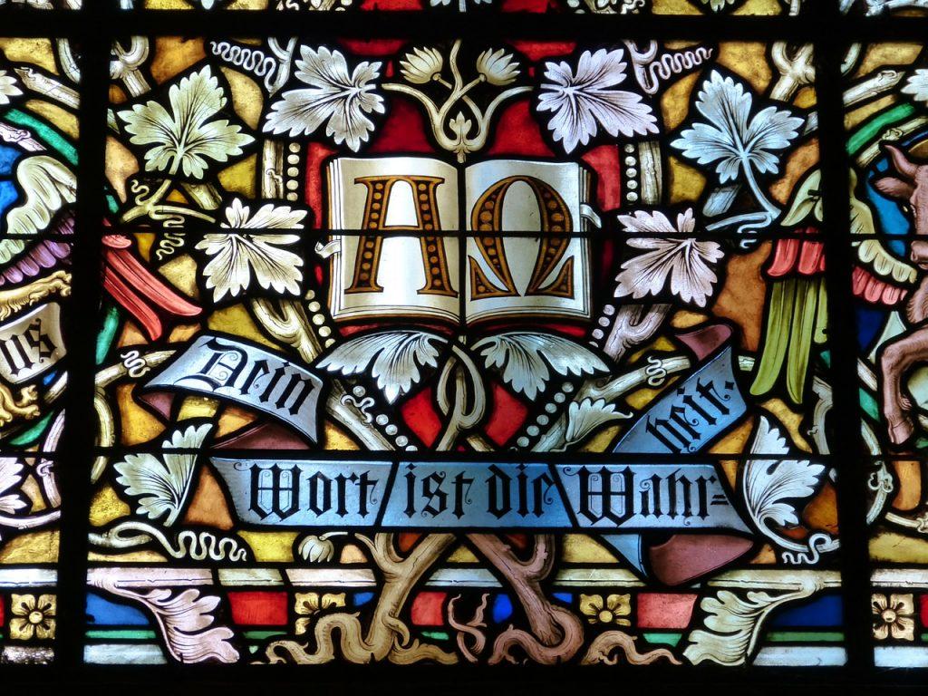 """Kirchenfenster mit Weinblättern und den Schriftzürgen """"Alpha-Omega"""" sowie """"Dein Wort ist die Wahrheit"""""""