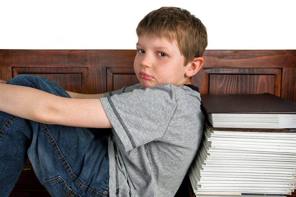 Ein Junge sieht traurig aus und hockt auf einer Bank mit dem Rücken zu Schulbüchern