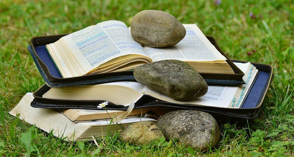 Jesus - ein Stolperstein? Das Bild zeigt aufgeschlagene Bibeln, auf denen Steine liegen