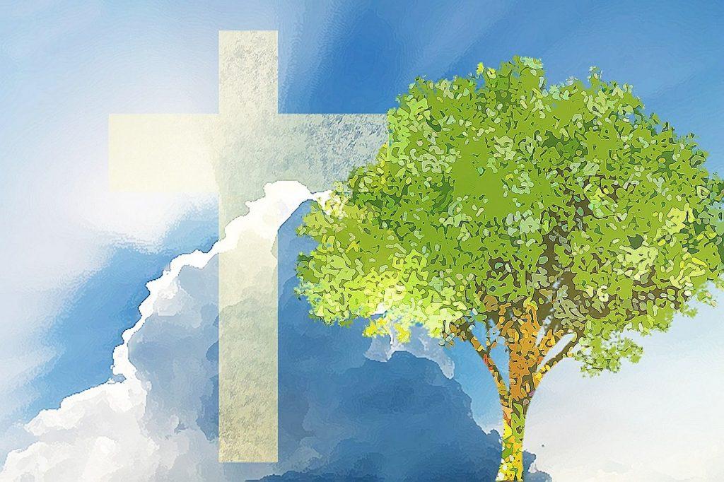 Ein weißes Kreuz vor blauem Himmel, daneben ein grüner Baum