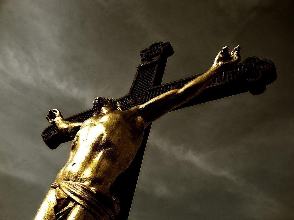 Ein vergoldeter Christus an einem schwarzen Kreuz aus Metall