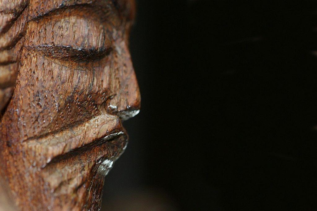 Weinen kann nur der, der liebt: Nur das traurige Gesicht Jesu, eine grobe Holzschnitzerei, im Profil vor schwarzem Hintergrund rechts