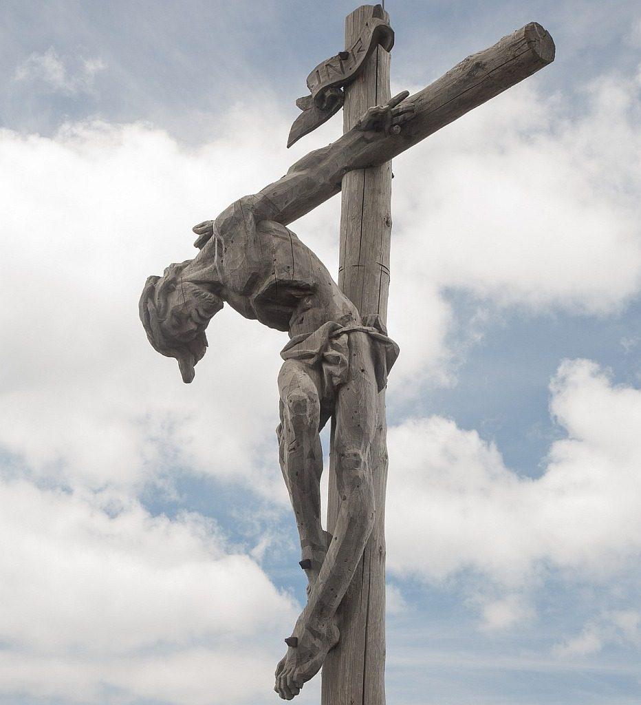Jesus hängt vornüber gebeugt und verrenkt an einem Gipfelkreuz aus schlichten Pfählen