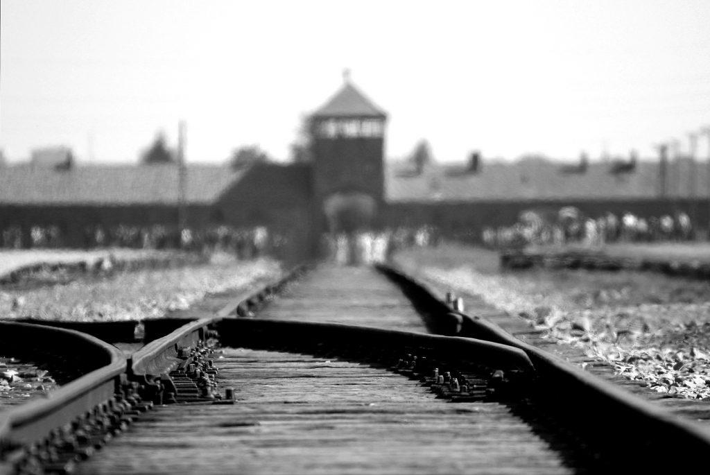 Schluss mit der Vergangenheitsbewältigung? Ein Blick auf das Vernichtungslager Auschwitz-Birkenau, unscharf, davor Schienen mit einer Weiche, die nach links abbiegt