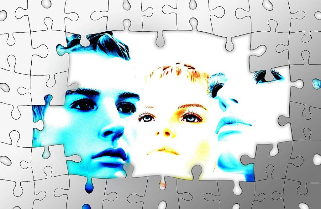 Können wir aus unserer Haut heraus? Ein Bild aus Puzzle-Teilen ohne Bilder, in deren Mitte die Teile fehlen und drei Gesichter zu sehen sind