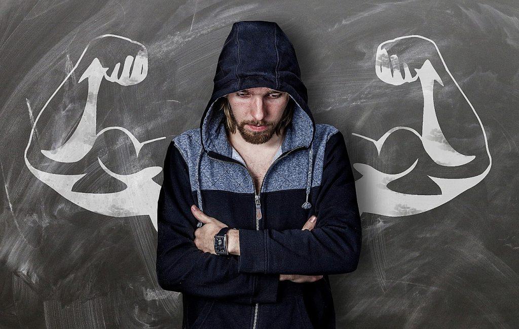 Stark sein: ein junger Mann steht mit verschränkten Armen und gesenktem Blick vor einer Tafel, auf der hinter ihm Bizeps-bepackte Arme posieren