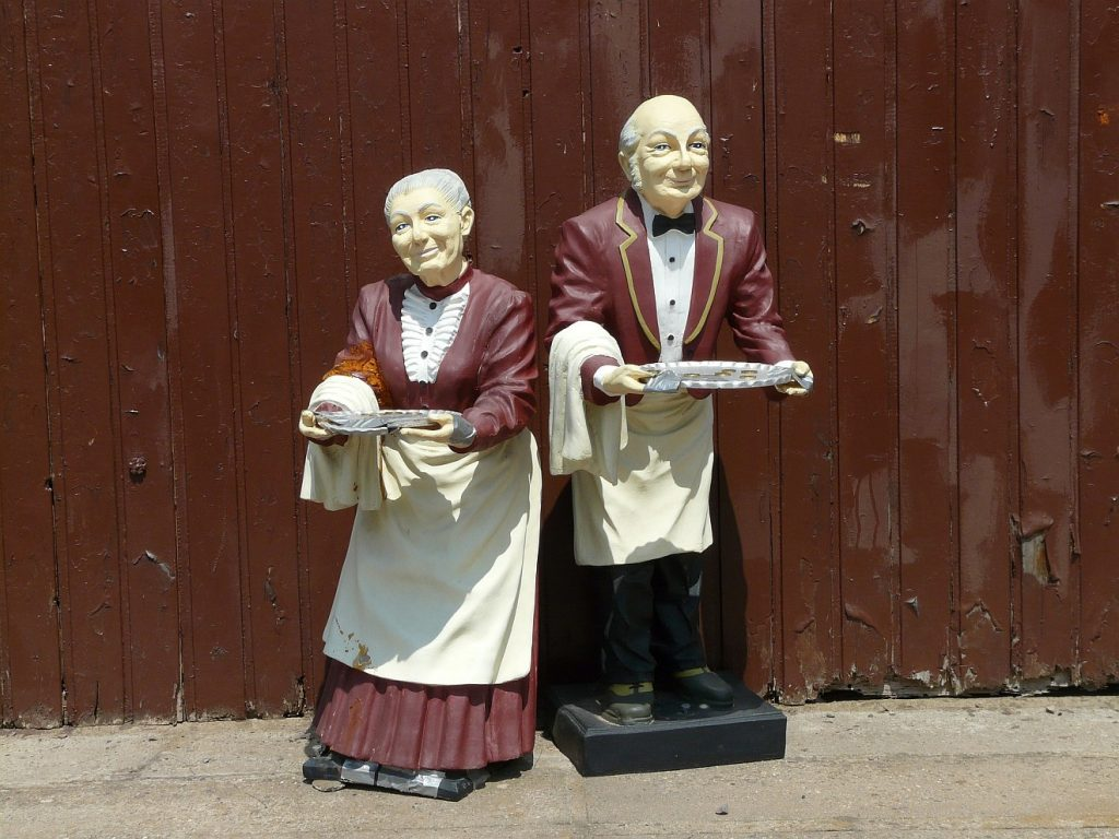 Zwei Figuren einer Dienerin und eines Dieners, die ein Tablett vor sich hertragen