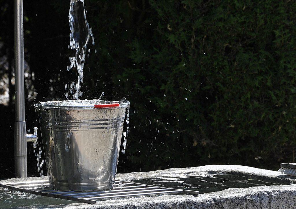 Ein Eimer mit Wasser, aus dem Wasser überläuft, so dass Tropfen auch am Eimer sind