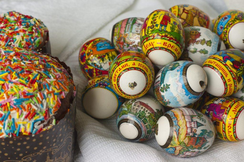 Ostereier mit russischer Aufschrift neben süßem Gebäck