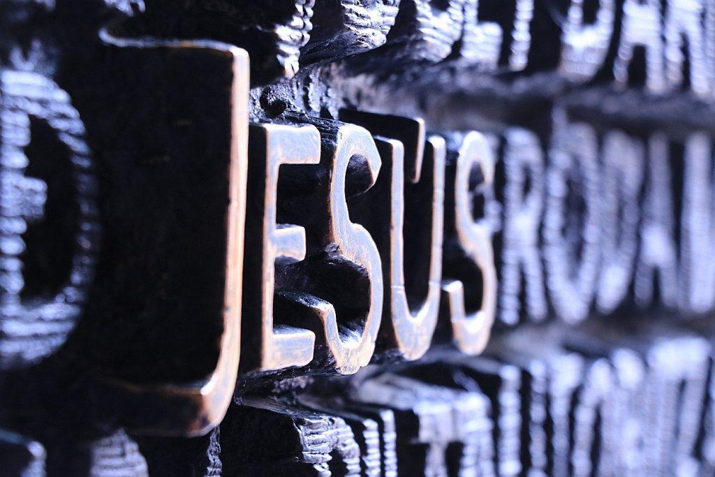 """Was haben wir von Jesus zu erwarten? Auf dem Bild ist ein hervorgehobener Schriftzug """"Jesus"""" als Relief zu sehen"""