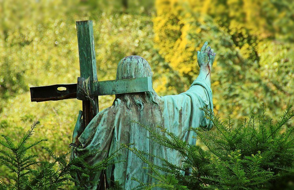 Statue von Jesus, grün überzogen, von hinten, er segnet mit der Rechten, in der Linken trägt er sein Kreuz
