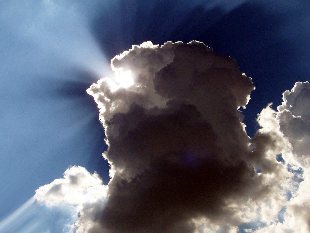 Eine aufgetürmte Wolke, hell und dunkel, durch die die Sonne hindurchscheint