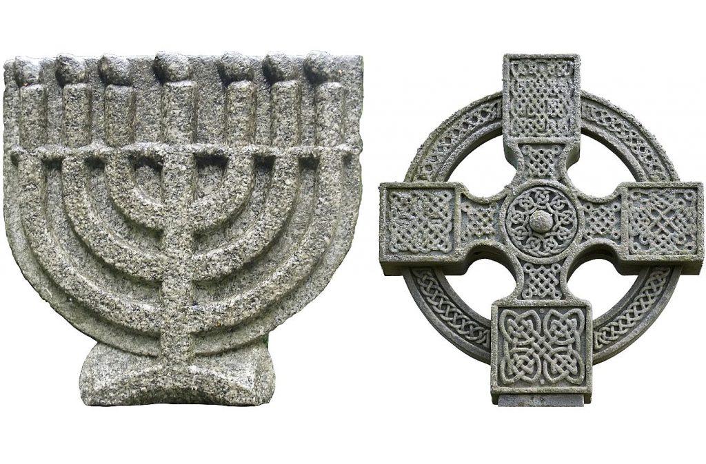 Eine Menora und ein Kreuz - jeweils in Stein gemeißelt oder aus Stein gefertigt