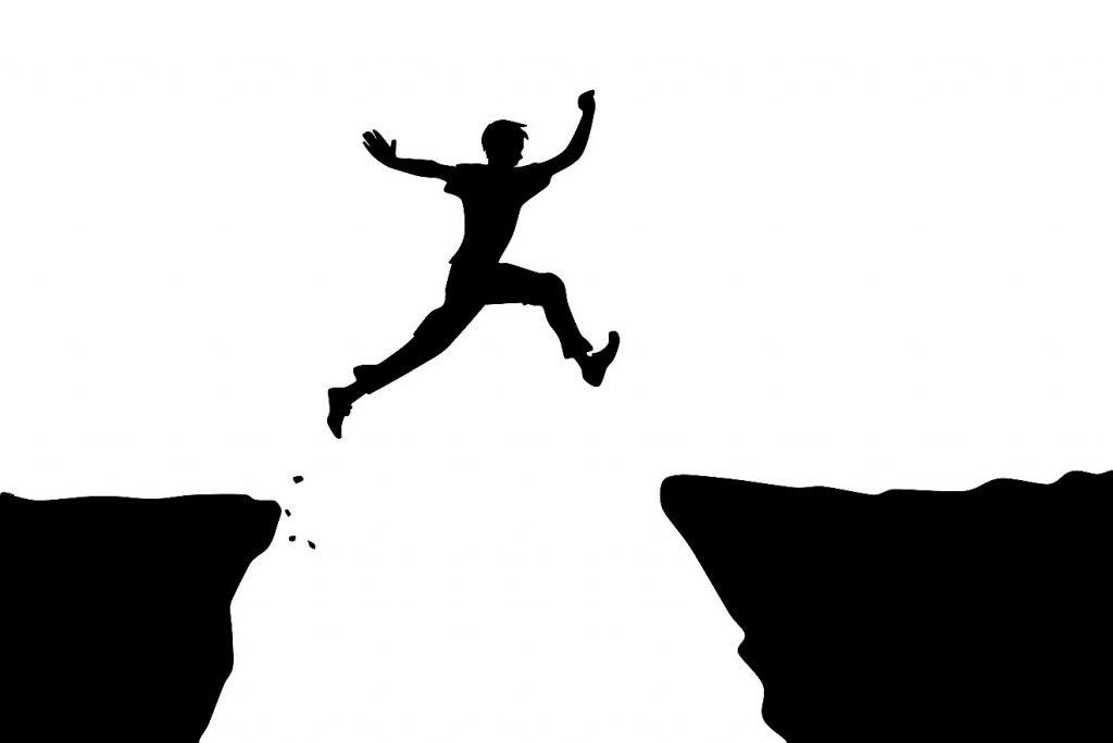 Angst durch Mut überwinden: Silhouette eines Mannes, der über einen Abgrund springt
