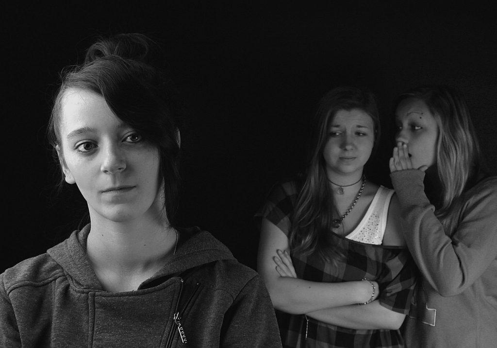 Wie leicht kommt man ins Gerede anderer Leute: Zwei Mädchen tuscheln über ein anderes Mädchen hinter deren Rücken
