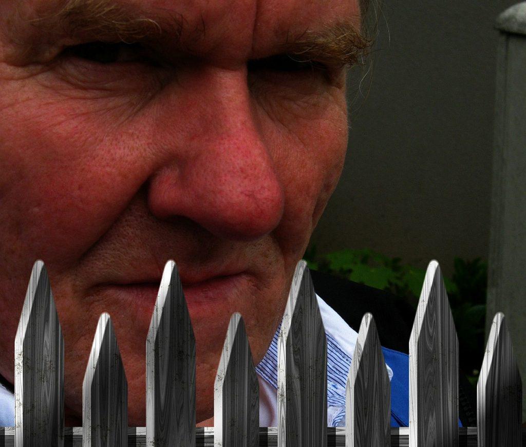 Ein misstrauisch blickender Mann hinter einem Staketenzaun