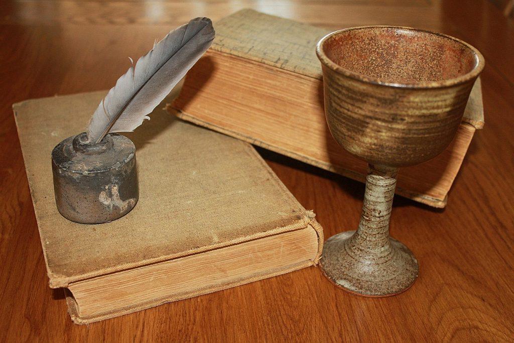 Ein alter Kelch neben einem Tintenfaß mit Feder und zwei alten Büchern
