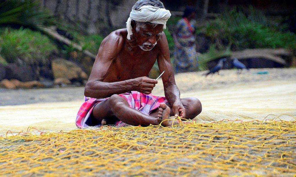 Ein Fischer in Indien, der am Strand ein Netz flickt