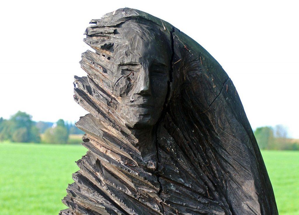 Die Skulptur ist scheinbar grob aus einem Holz herausgehackt, nur rechts ist sie glatt.