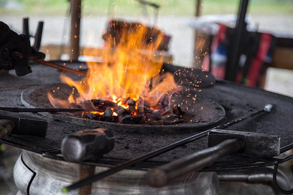 In der Schmiede wird die Gewalt von Feuer und Hammer besonders sinnfällig - ein Hammer liegt neben der Feuer-Esse