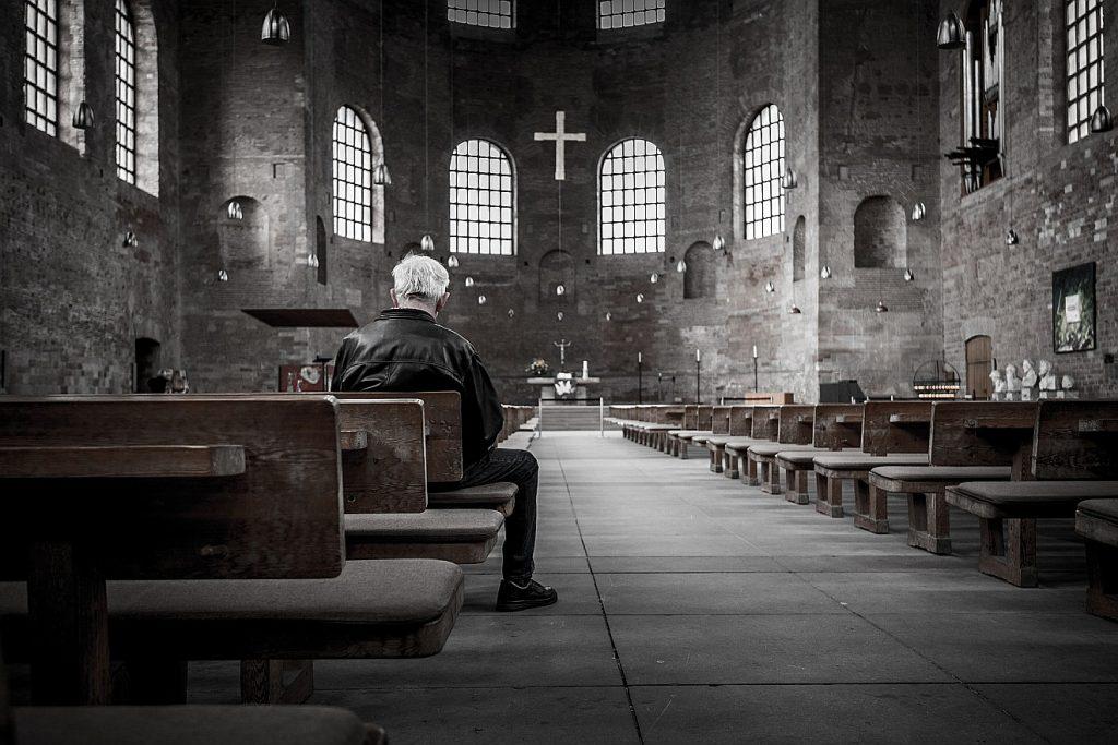 Eine Woche vor der Festwoche denke ich über den Kirchenbesuch nach: Bild eines Mannes in der Kirchenbank einer alten Kirche