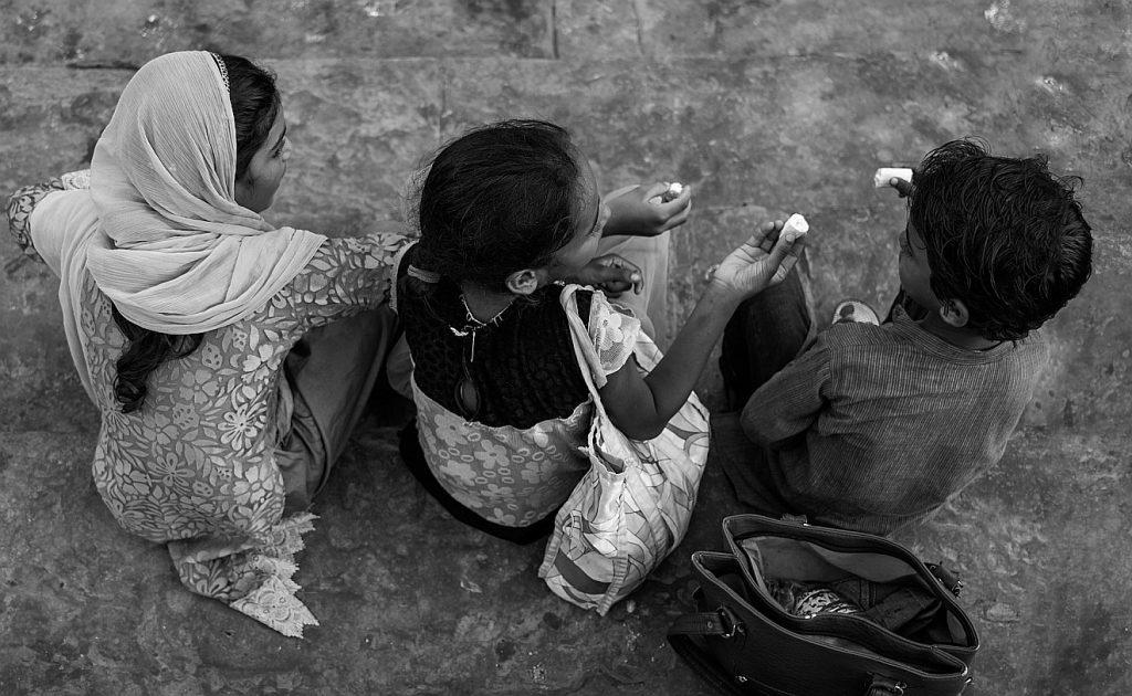 Wer für wenig dankbar ist, kann auch teilen: Drei Kinder sitzen nebeneinander und teilen etwas miteinander