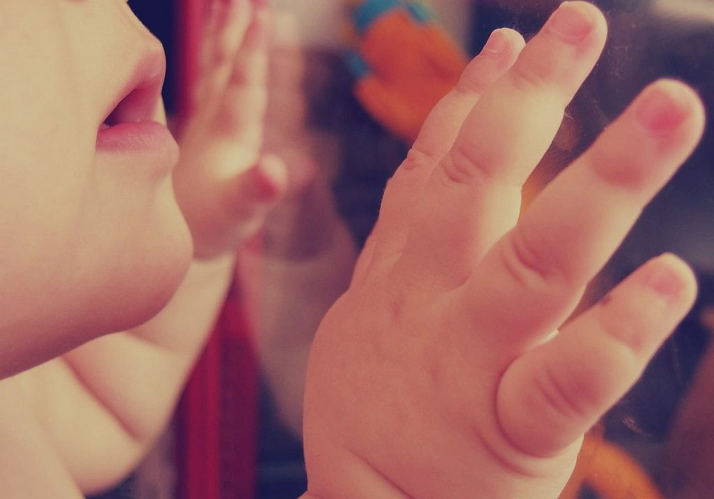 Der Mund eines Babys und seine Hände sind zu sehen