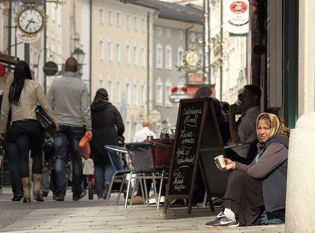 Eine Bettlerin hockt in einer Fußgängerzone