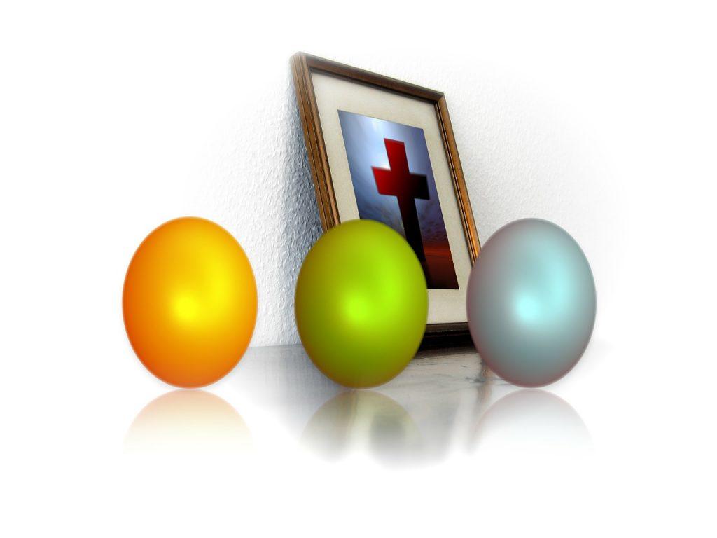 Drei unterschiedlich gefärbte Ostereier vor einem Kreuz