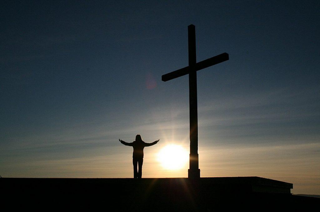 Gott glaubt an uns: Ein Mensch mit ausgebreiteten armen neben einem Kreuz bei Sonnenaufgang
