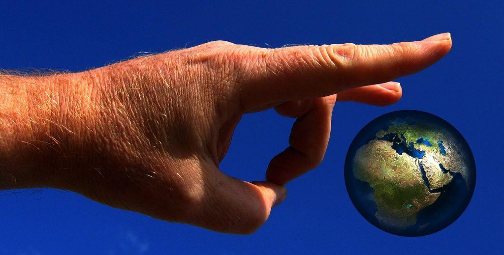 Eine Hand ist dabei, die Erde wegzuschnipsen