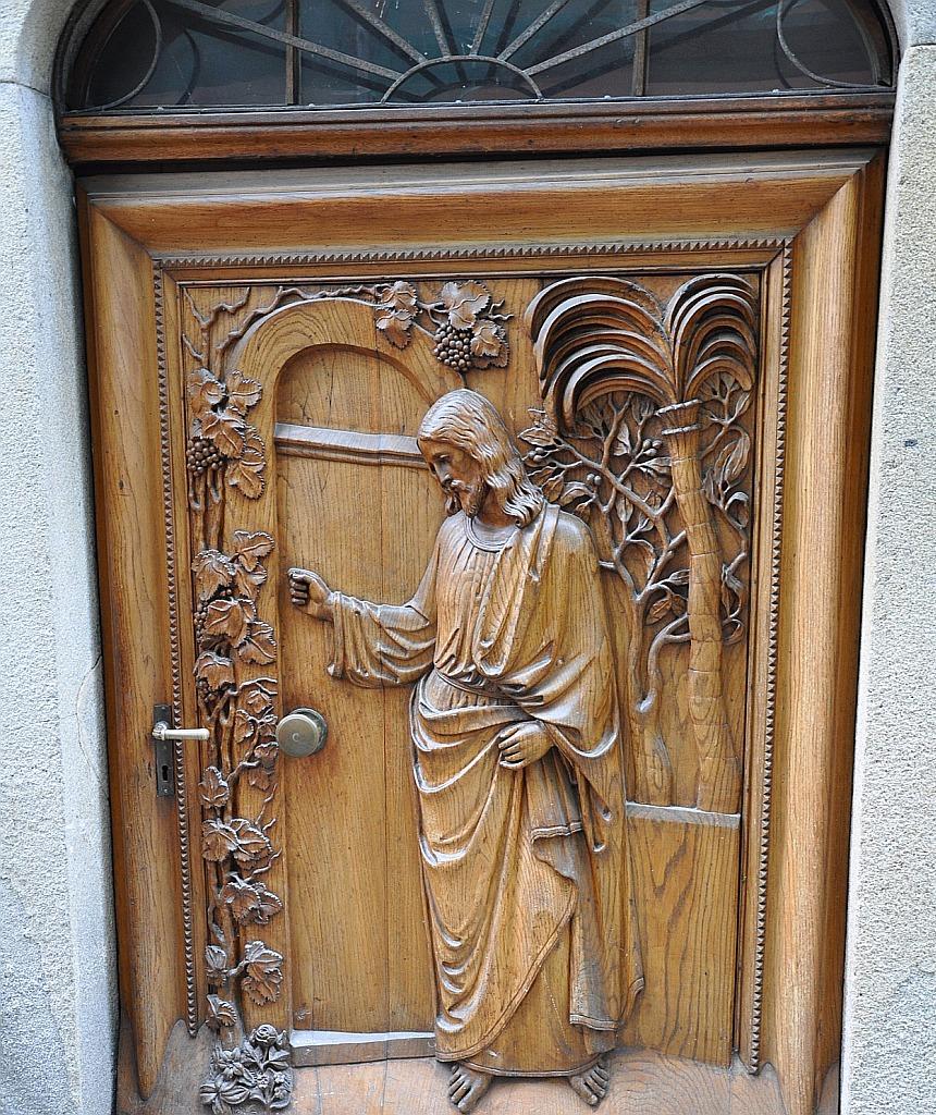 Eine Tür, auf der Jesus als Holzrelief dargestellt ist, rechts von ihm eine Palme, links scheint er mit der Hand die Türklinke herunterdrücken zu wollen