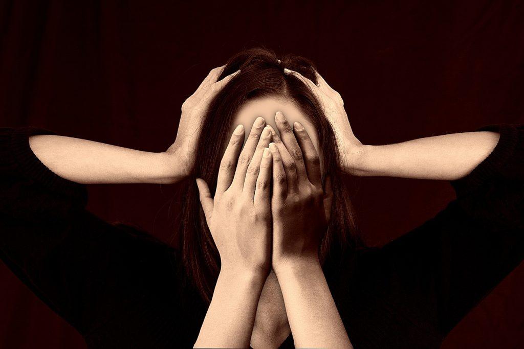 Schäme dich nicht! Das Bild zeigt eine Frau, die zwei Hände vor ihr Gesicht hält und zwei weitere Hände auf ihrem Kopf liegen hat