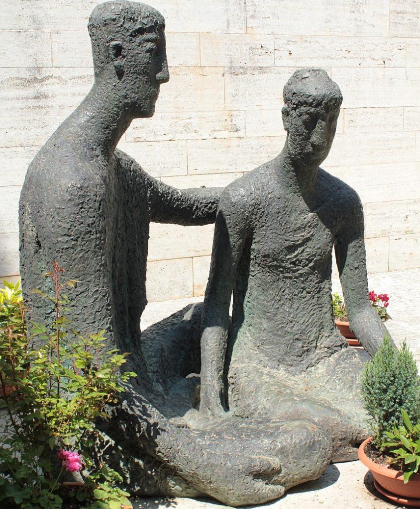 Ein Mahnmal, das zwei sitzende Männer zeigt, von denen der eine dem anderen den Rücken stärkt