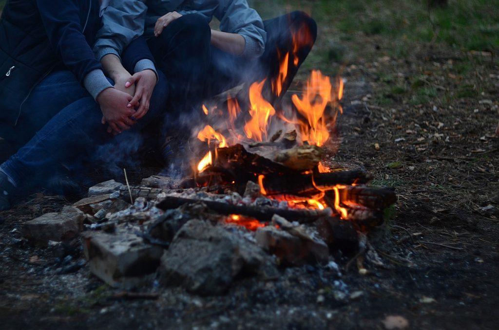 Wärmende Gemeinschaft: Ein Lagerfeuer, neben dem Menschen sitzen, die einander die Hände halten und wärmen
