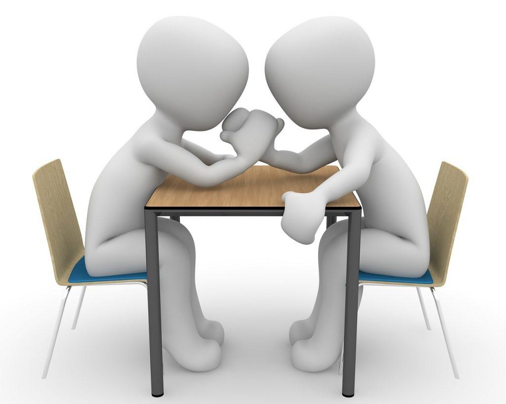 Zwei Männchen sitzen am Tisch und machen Arm-Drücken