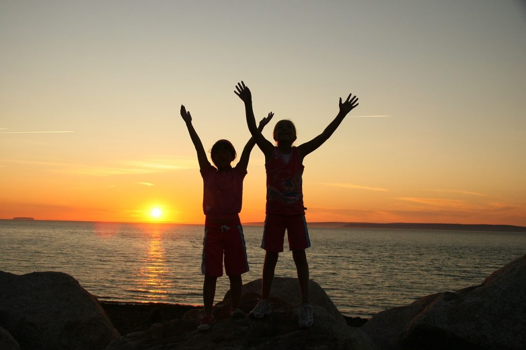 Zwei Kinder werfen vor dem Sonnenuntergang die Arme in die Höhe