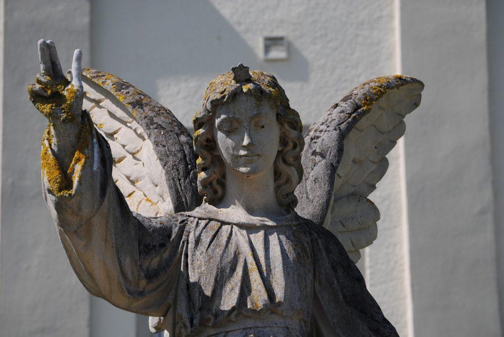 Die Steinskulptur eines Engels in weiblicher Gestalt, der die Hand segnend erhebt