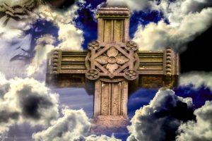 Ein wuchtiges Steinkreuz in den Wolken mit dem Gesicht des Christus mit der Dornenkrone daneben