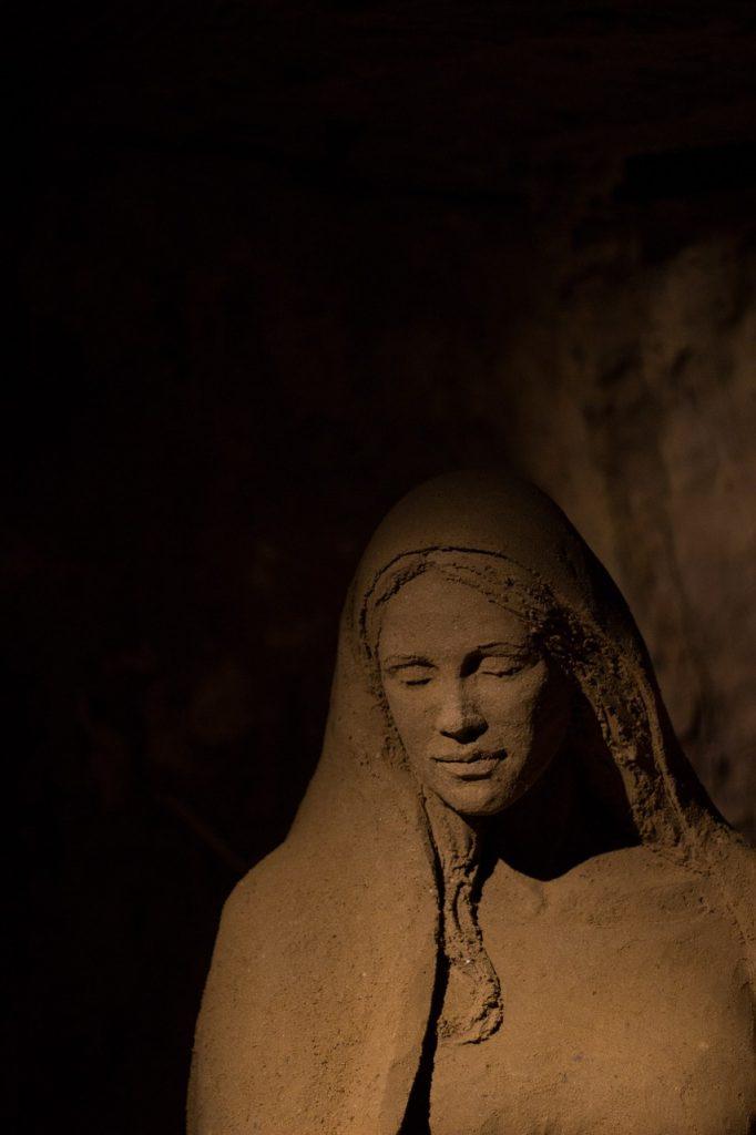 Sandskulptur eines jungen Mädchens, die im Dunkeln steht
