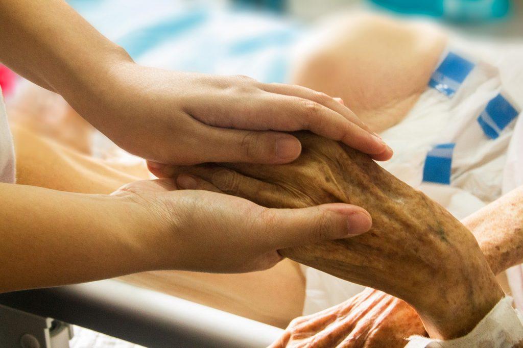 Hände einer Pflegeperson halten die Hand eines alten Menschen im Krankenbett