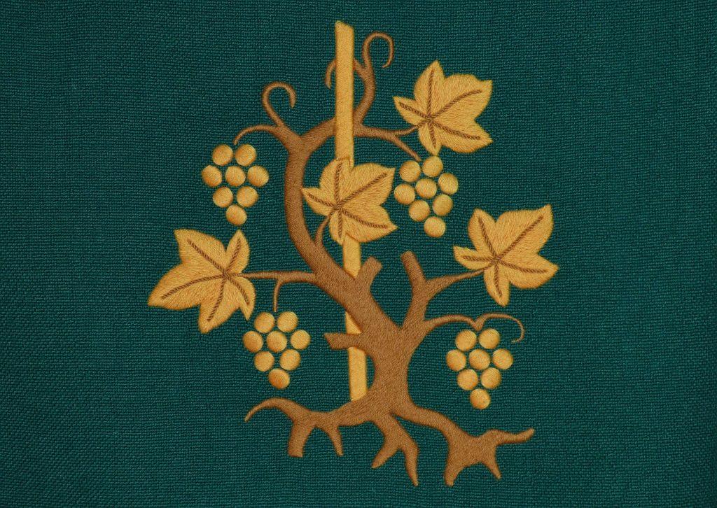 Ein Altarbehang mit einem Weinstock und seinen Reben, an denen Trauben hängen