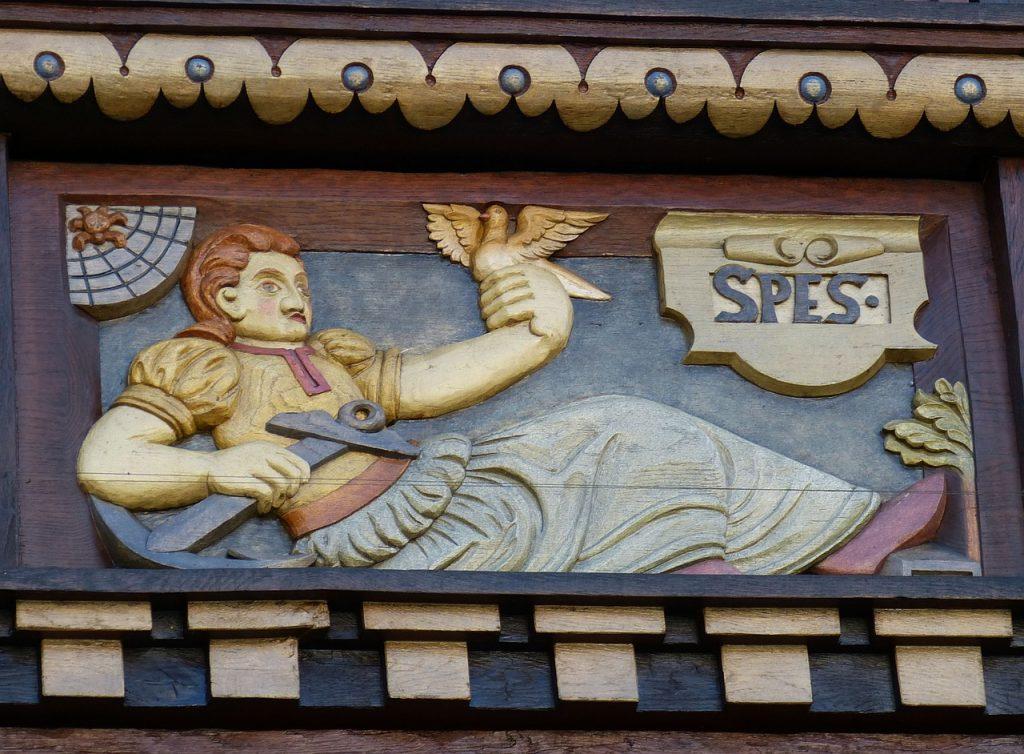 """Ein liegender Soldat, der ein Schwert an der Schneide hält, in der anderen Hand eine Taube; links oben eine Spinne im Netz, recht oben der Schriftzug """"spes"""" = """"Hoffnung"""", rechts unten grünende Blätter"""