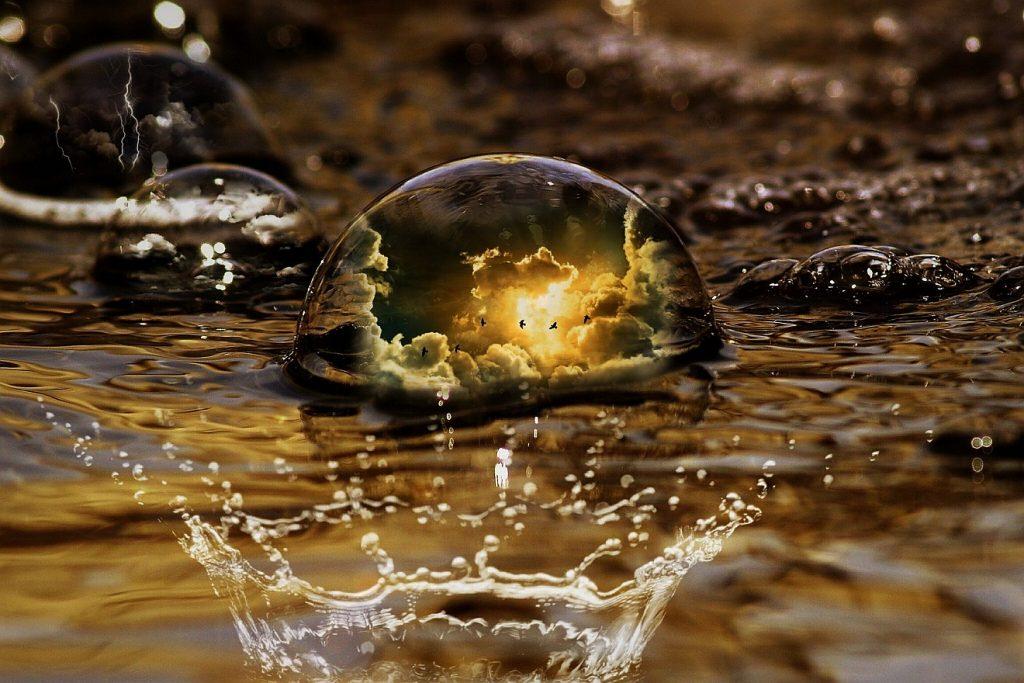 Gottes Welt mit Regen und Sonnenschein spiegelt sich in einem großen Wassertropfen in einer Pfütze