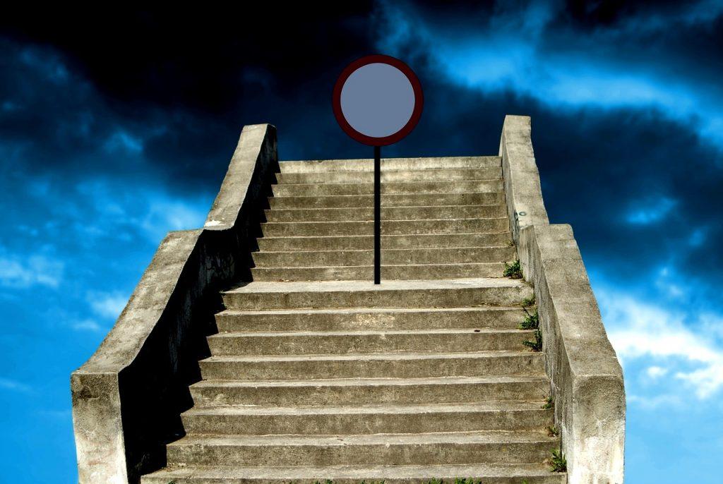 Eine alte Betontreppe führt hinauf zum blauen Himmel, der aber dunkel bewölkt ist, und vor dem letzten Treppenabsatz steht ein Durchfahrt-Verbotsschild